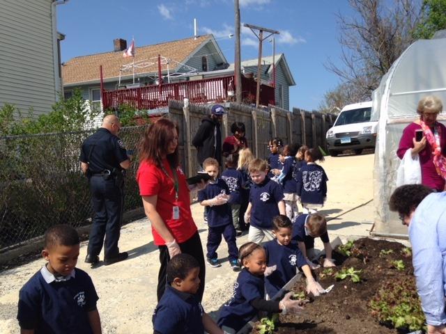 A group of children and volunteers work in the Brass City Harvest urban garden in Waterbury, Connecticut.