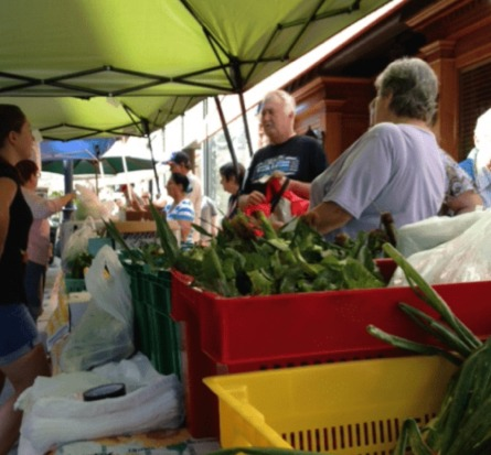 A group of customers shopping at a farmers' market.